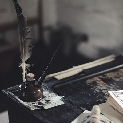 An image with an inkwell and feather quill sitting on the edge of a weathered writing desk. Nearby are yellowing pieces of parchment.