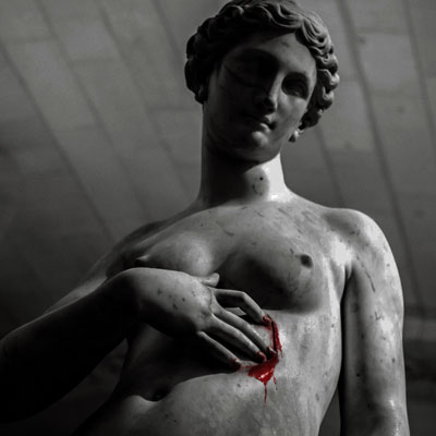 A nude, marble statue of a woman, fashioned in a greek style. One of her hands is pressed to her ribcage where blood dribbles from what appears to be a wound.
