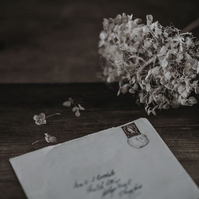 An image of a envelope with old-fashioned, caligraphy handwriting on the front. The envelope is on a wooden table with a dried hyacinth flower nearby.